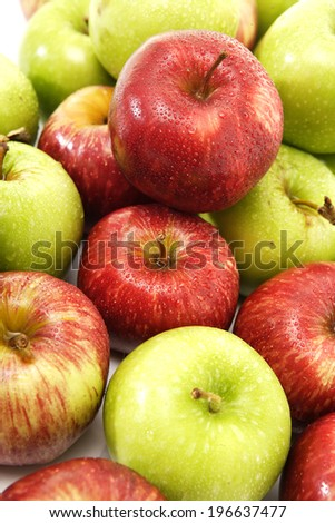 A closeup view of a pile of green and red apples