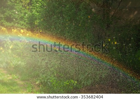 A closeup view of a rainbow and water drops from a lawn sprinkler spraying water - stock photo