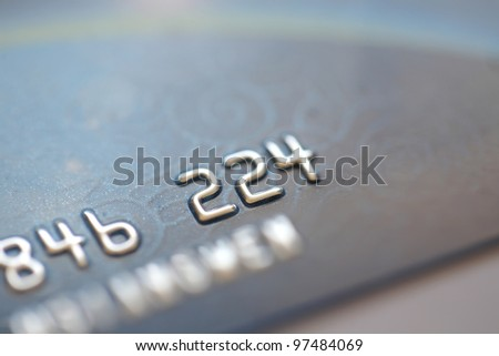 A closeup view of digits on a credit card, silver digits on blue / grey card, macro view