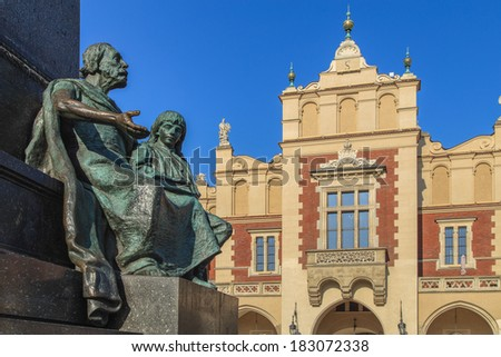 A closup of a statue of Adam Mickiewicz landmark on a Main Square with Sukiennice building in a background in Cracow, Poland - stock photo
