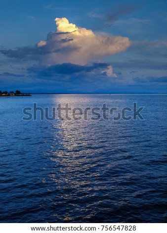A cloud at dusk casts a reflection in the ocean in eastern Thailand