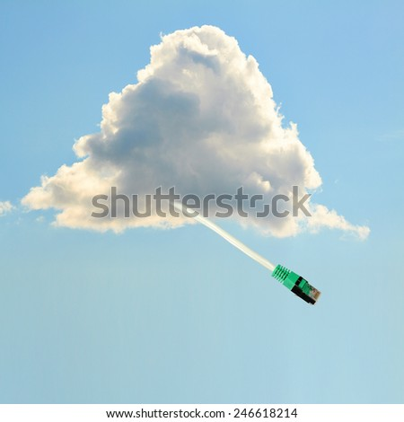 A cloud with data cable flying befor a light blue background. - stock photo