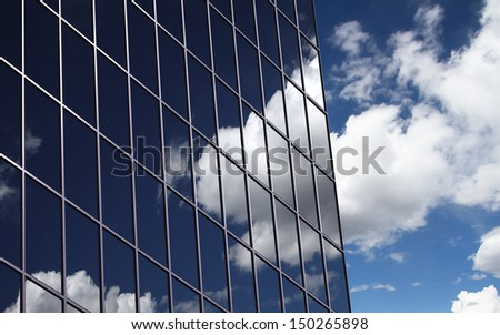 A clouds reflection in glass wall of skyscraper - stock photo