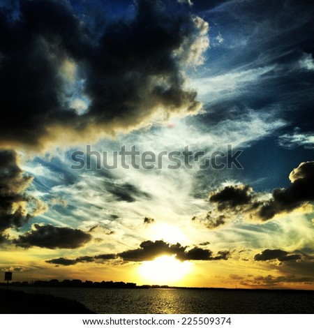 A cloudy sky with the sun setting over the silhouette of a city and water. - stock photo