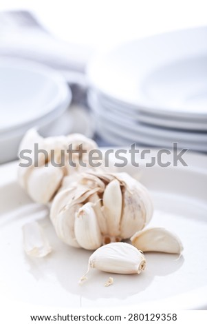 a clove of garlic on a plate - stock photo