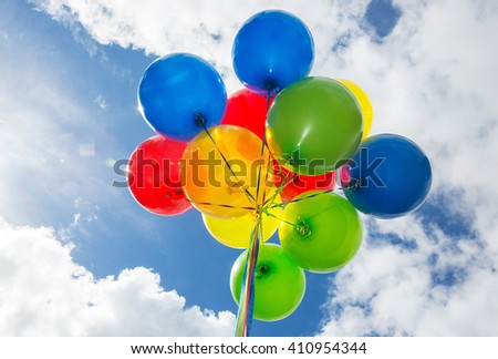 A cluster for blue, red, yellow and green helium balloons floating under a blue sky with white clouds on a sunny.