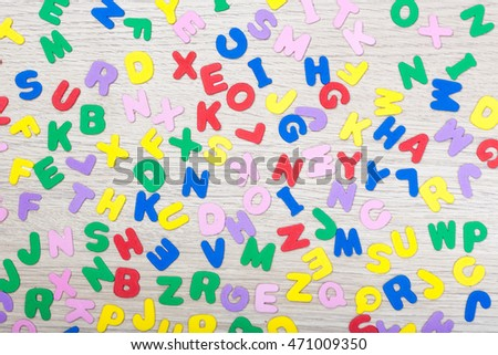 A cluster of colored letters on wooden table with the word school. studioshot.