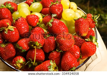 A cluster of freshly ripened strawberries with white grapes