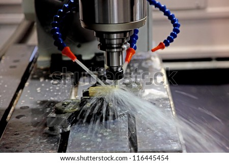 A CNC milling machine milling heads in metal industry - stock photo