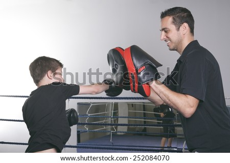 A coach with a child learning boxe - stock photo