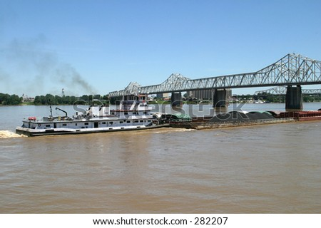 A coal barge, loaded with coal, steaming up the ohio river, passing under a bridge. - stock photo