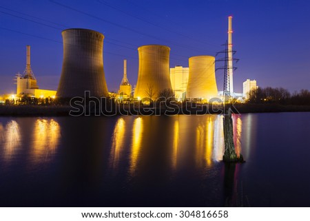 A coal-fired power station in river landscape with dead trees at night
