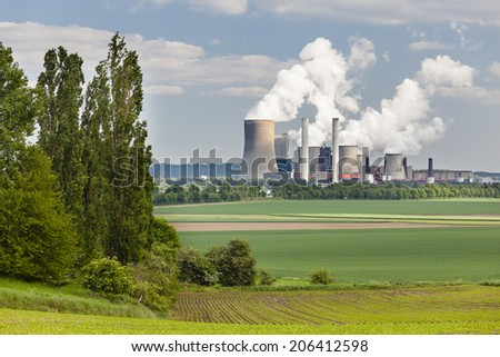 A coal-fired power station in the distance in agricultural landscape. The power station Niederaussem has the second highest cooling tower in the world with a height of 200m. - stock photo