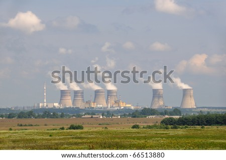 A coal-fired power station with beautiful blossom field and blue sky. - stock photo