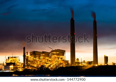 A coal power plant lit up at night - stock photo