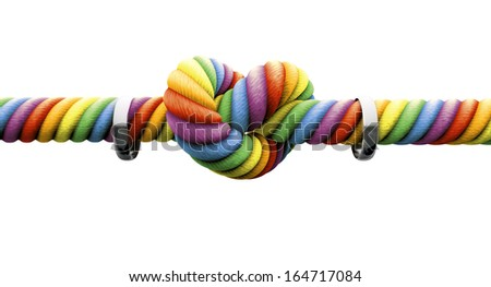 A coarse rope in the colors of the homosexual flag with a knot tied in the middle and two silver rings hanging on it on an isolated background - stock photo