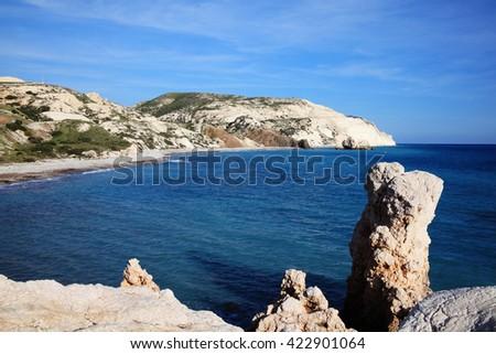A coastline shoreline bay close to Aphrodite's Rock showing the Mediterranean sea with a blue sky and sea - stock photo