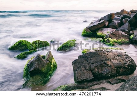 A coastline with big stones in the water. Motion photography. The stones are covered with moss. Pure nature.