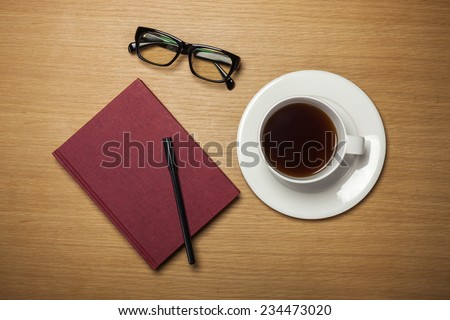 A coffee and cup and a plate and a book, pencil, glasses on the wood table(desk), top view at the studio.