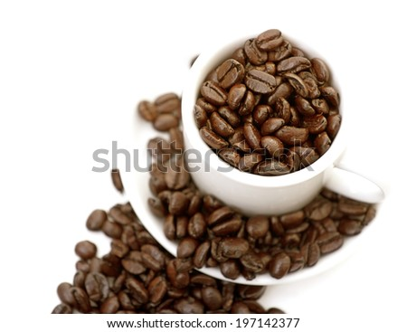 A coffee cup and saucer are overflowing with coffee beans.