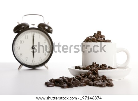 A coffee cup and saucer overfilled with coffee beans. - stock photo