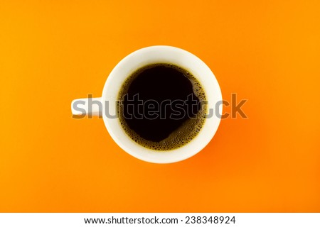 A coffee cup shot from above on a bright orange background. - stock photo