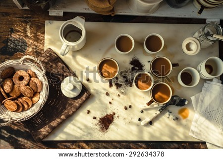 A coffee drink breakfast family concept. Concept include many cups with cappuccino and coffee drink situated over a marble rustic kitchen table with basket of biscuits from above. Rustic still life. - stock photo