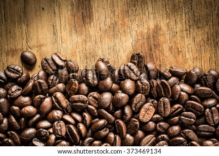 A coffee mug of coffee beans on wooden table - stock photo