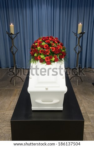 A coffin with a flower arrangement in a morgue and a burning candle in front - stock photo