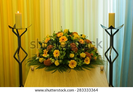 A coffin with a flower arrangement in a morgue with two burning candles - stock photo