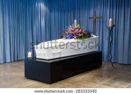 A coffin with a flower arrangement in a morgue with two burning candles and a cross
