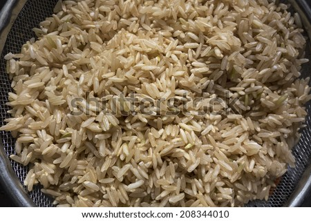 A colander with uncooked brown rice.  - stock photo