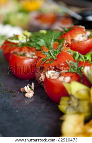 A cold buffet with the stuffed tomatoes in focus - stock photo