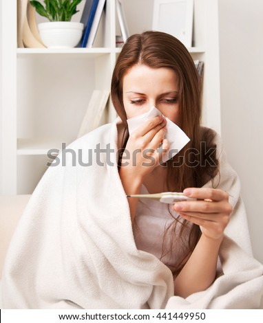 a cold girl blows her nose, and measures the temperature in a room sitting on a chair at the cabinet - stock photo