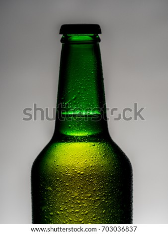 A cold green beer bottle with water drops