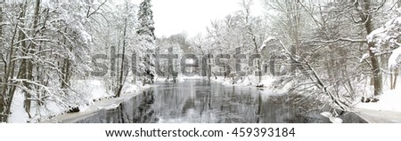 A cold river flowing placidly through a frozen Swedish landscape. - stock photo