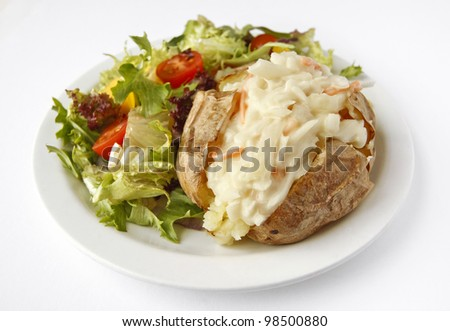 A Coleslaw baked potato on a plate with side salad - stock photo