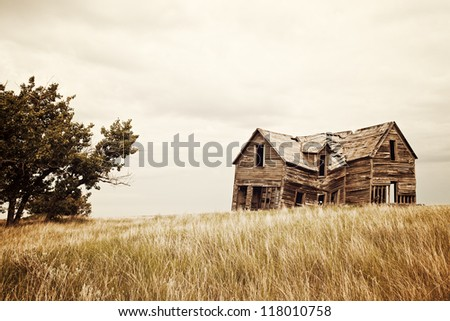 A collapsing old house on the prairies. - stock photo