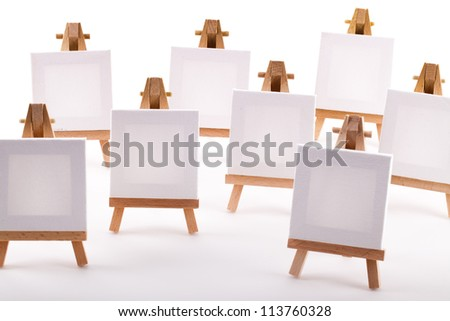A collection of blank canvases on mini easels on a white background