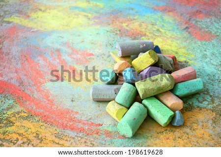 a collection of colorful sidewalk chalk is piled up on a rainbow drawing, outside on the pavement. - stock photo