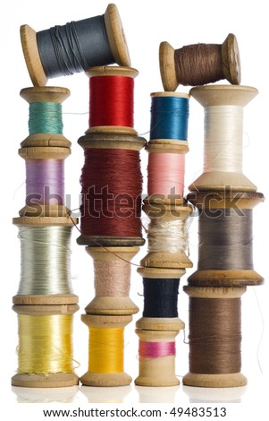 a collection of colorful spools of thread on white - stock photo