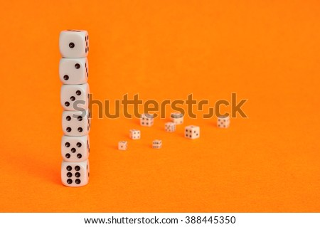 A collection of dices that is displayed on an orange background with some out of focus in the background - stock photo