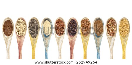 a collection of gluten free grains and seeds on isolated wooden spoons - kaniwa, sorghum, chia, amaranth,red quinoa, black quinoa, brown rice, teff, buckwheat, gold flax (from left to right) - stock photo