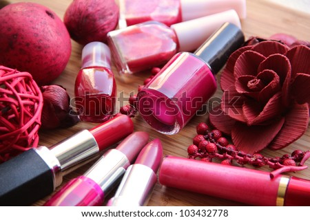 A collection of makeup: lipsticks, lip gloss and nail polishes decorated with red potpourri all in red and pink shades - stock photo