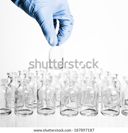 A collection of many small empty scientific vials in rows with a hamd wearing a blue latex glove holds one container up.