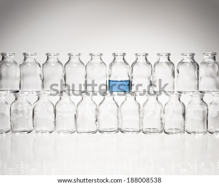 A collection of many small empty scientific vials stacked in rows against a white background with one vial partly filled with light blue liquid. - stock photo