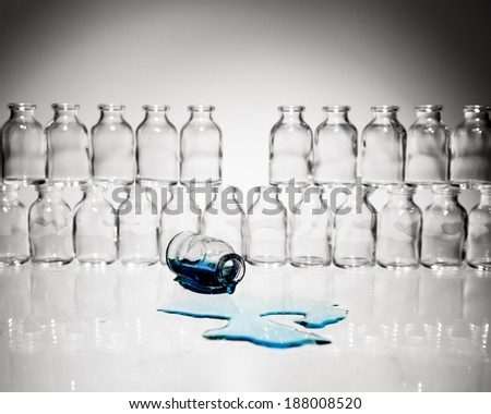A collection of many small empty scientific vials stacked in rows with one vial lying on its side spilling out a light blue liquid. - stock photo