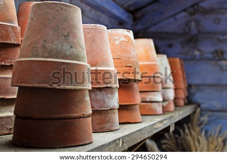 A collection of plant pots on a shelf in a potting shed, illuminated by the light from an open door - stock photo