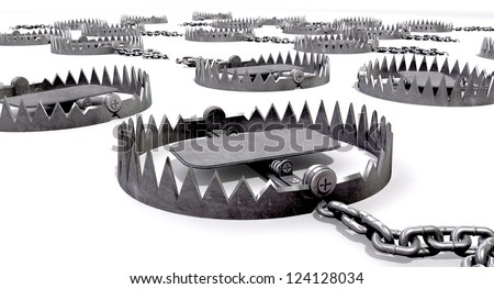 A collection of randomly set out metal animal traps attached to the ground with metal chains on an isolated background - stock photo