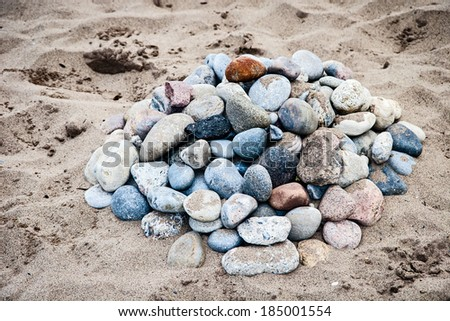 a collection of stones on sand at the beach in summertime - stock photo